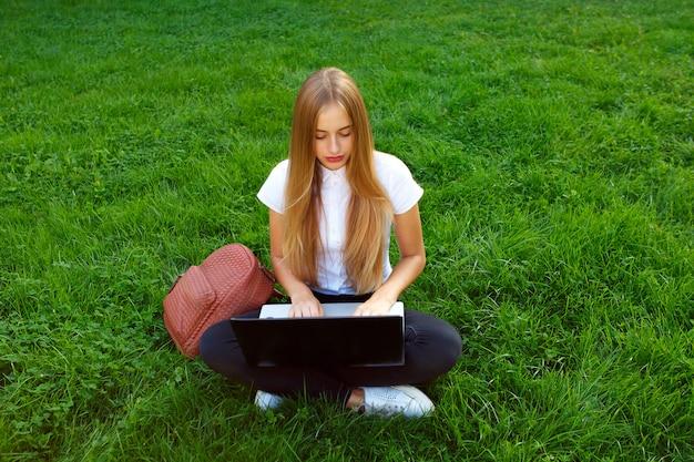 Piękna młoda dziewczyna siedzi w parku na zielonej trawie z laptopem