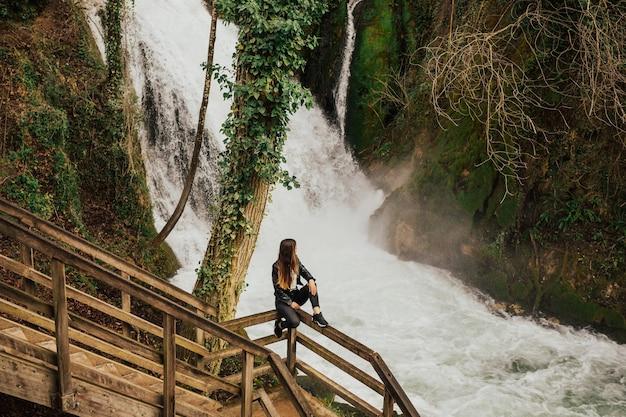 Piękna, młoda dziewczyna siedzi w pobliżu niesamowitego wodospadu w terni we włoszech.