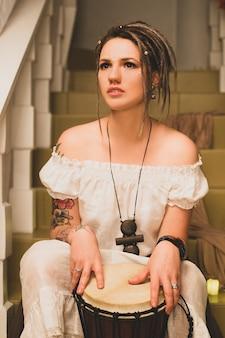 Piękna, młoda dziewczyna siedzi w pozie jogi i medytacji z bębnem
