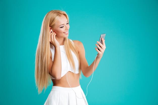 Piękna, młoda dziewczyna słuchania muzyki ze słuchawkami i smartfonem na białym tle na niebieskiej ścianie
