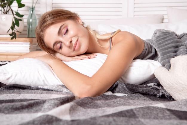 Piękna młoda dziewczyna śpi w sypialni.