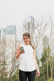 Piękna młoda dziewczyna sprawdza jej smartphone