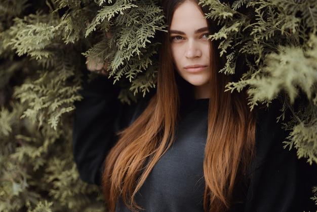 Piękna młoda dziewczyna stoi na tle zielonej trawie. drzewo tui