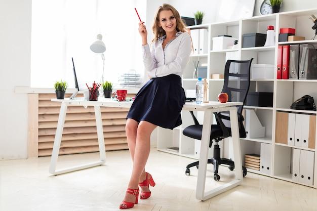 Piękna młoda dziewczyna stoi przy stole w biurze i trzyma w rękach czerwony ołówek.