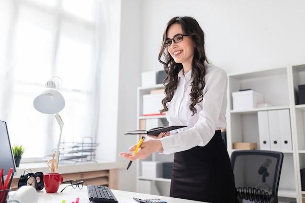 Piękna młoda dziewczyna stoi w pobliżu biurka i trzyma w rękach długopis i notatnik. dziewczyna negocjuje.