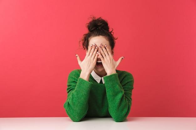 Piękna młoda dziewczyna student siedzi przy stole na białym tle, zakryć twarz