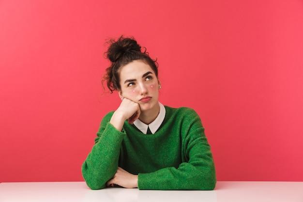Piękna młoda dziewczyna studentka siedzi przy stole na białym tle, odwracając wzrok