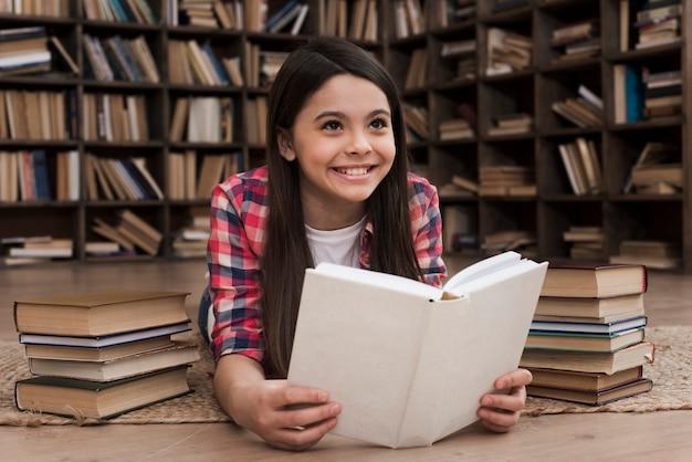 Piękna młoda dziewczyna studiuje w bibliotece