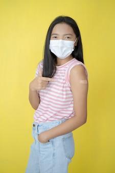 Piękna młoda dziewczyna szczepienia, nosić maskę.