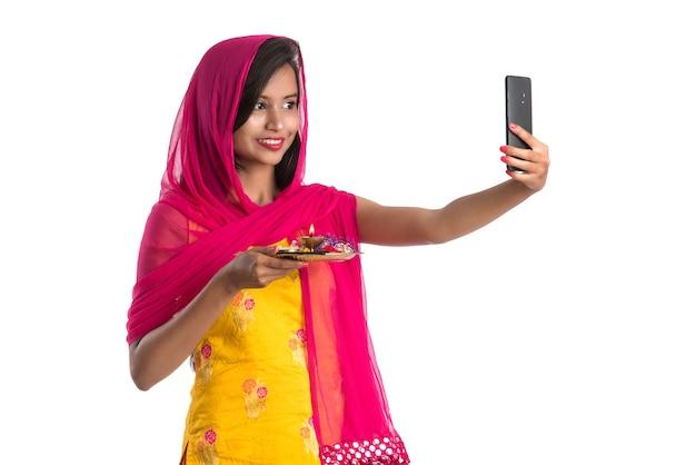 Piękna młoda dziewczyna szczęśliwa biorąc selfie z pooja thali za pomocą telefonu komórkowego lub smartfona