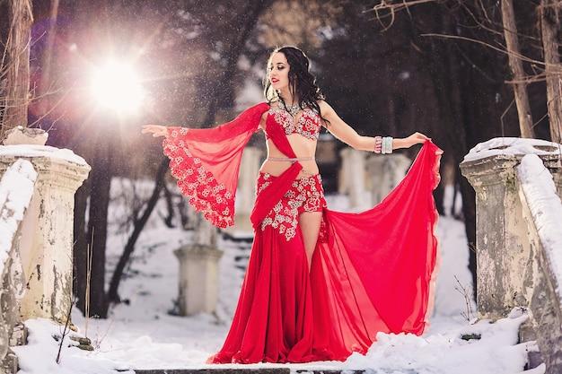 Piękna, młoda dziewczyna tańczy taniec brzucha w czerwonej sukience w zimie w parku na śniegu.