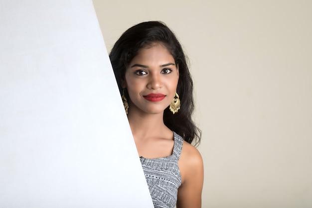 Piękna młoda dziewczyna trzyma biały duży szyld i pozowanie