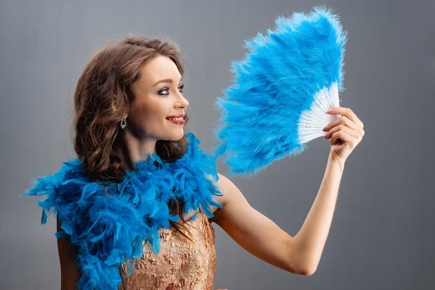 Piękna młoda dziewczyna trzyma fan piórka w jego ręce w błękitnym boa