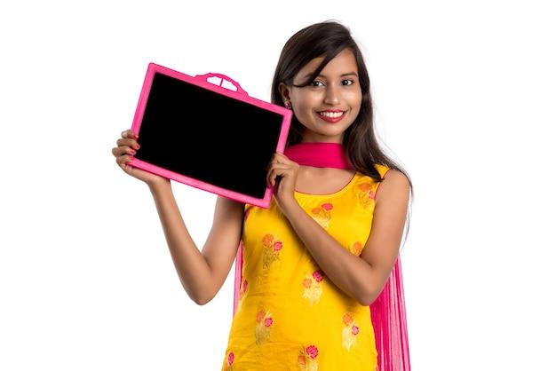 Piękna młoda dziewczyna trzyma i pokazuje coś na tablicy szkolnej lub łupków, na białym tle nad białym