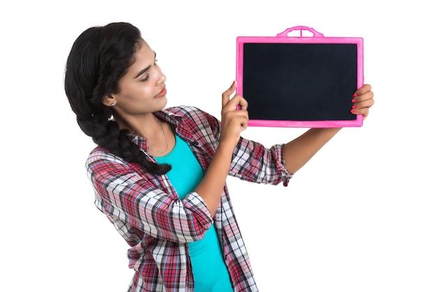 Piękna, młoda dziewczyna trzyma lub pozuje z tablicą łupkową na białej ścianie