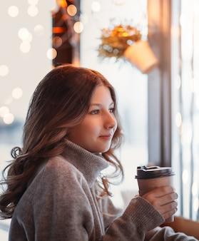 Piękna, młoda dziewczyna trzyma papierową filiżankę kawy i wygląda przez okno kawiarni