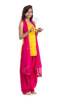 Piękna, młoda dziewczyna trzyma pooja thali i wykonywania kultu