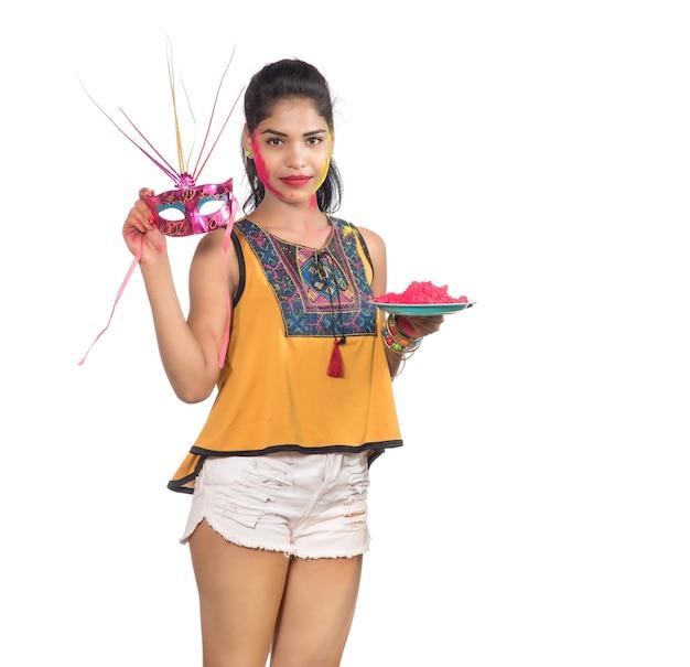 Piękna młoda dziewczyna trzyma pudrowany kolor w talerzu z maską karnawałową z okazji festiwalu holi.