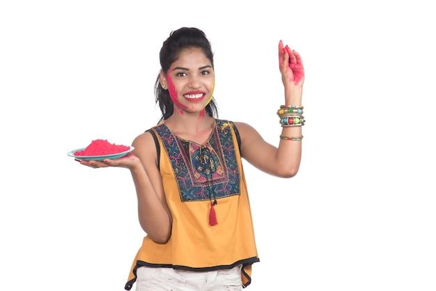 Piękna młoda dziewczyna trzyma sproszkowany kolor na talerzu i cieszy się kolory przy okazji festiwalu holi.