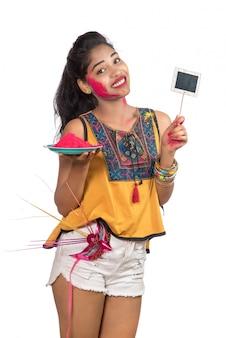 Piękna młoda dziewczyna trzyma sproszkowany kolor w talerzu z karnawałową maską i małym szyldem z okazji festiwalu holi.