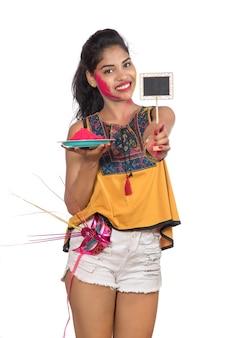 Piękna, młoda dziewczyna trzyma sproszkowany kolor w talerzu z maską karnawałową