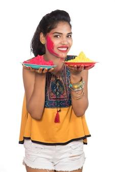 Piękna młoda dziewczyna trzyma sproszkowany kolor w talerzu z okazji festiwalu holi.