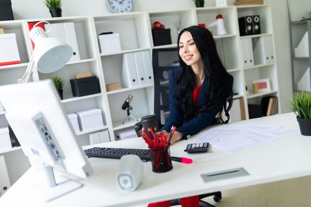 Piękna młoda dziewczyna trzyma szkło w jej ręce z kawą i pisać na maszynie tekst na klawiaturze