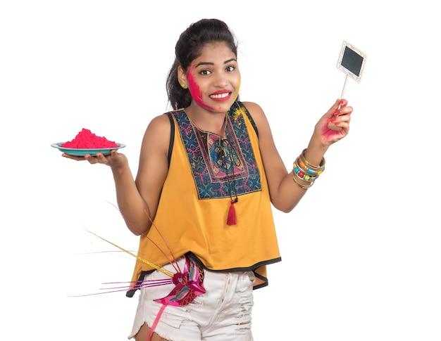 Piękna młoda dziewczyna trzymająca pudrowy kolor w talerzu z karnawałową maską i małą tablicą z okazji festiwalu holi.