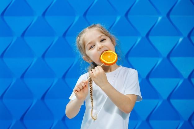 Piękna młoda dziewczyna ubrana w białą koszulkę trzyma w dłoniach pół pomarańczy i uśmiecha się. owoce pomarańczowe, gryzie pomarańczę i lubi.