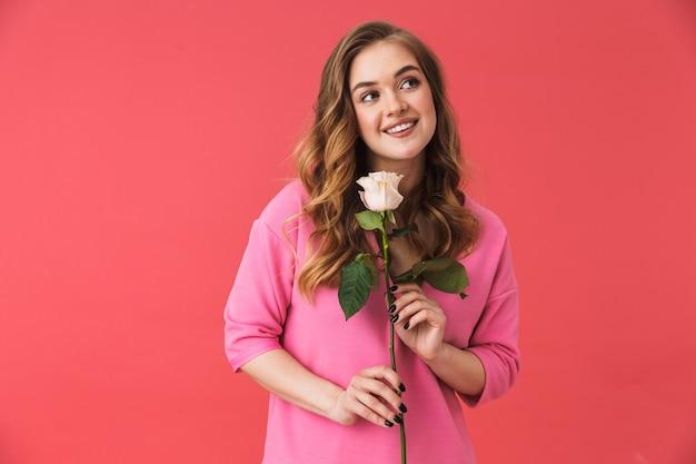 Piękna młoda dziewczyna ubrana w zwykłe ubrania, stojąca na białym tle nad różową ścianą, trzymająca różę
