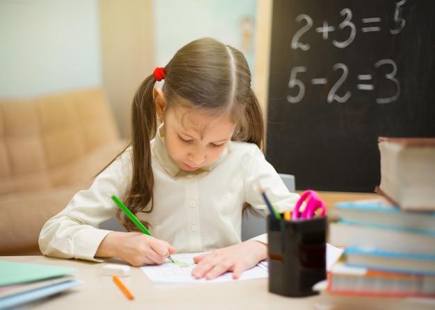 Piękna młoda dziewczyna uczy się w domu