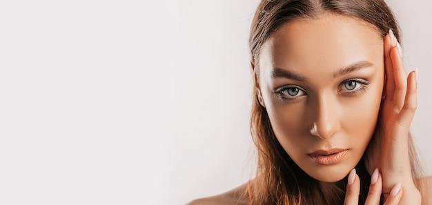 Piękna młoda dziewczyna uśmiechając się i pozowanie patrząc na kamery na białym tle na białym tle z makieta. pozytywna brunetki kobieta. miły wygląd. piękna twarz