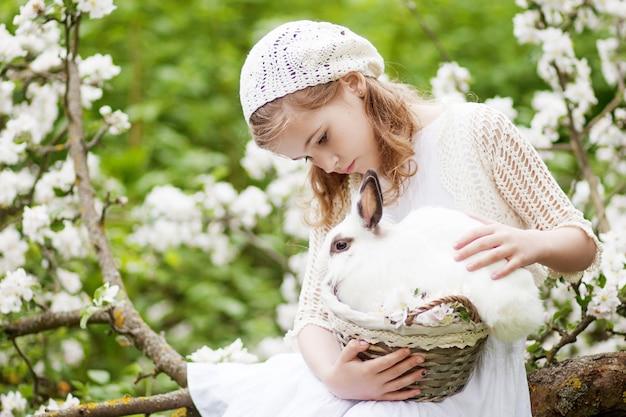 Piękna młoda dziewczyna w białej sukni, grając z białym królikiem w ogrodzie kwitnąć wiosną. wiosenna zabawa dla dzieci. czas wielkanocy