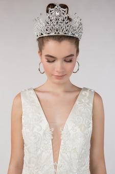 Piękna młoda dziewczyna w białej sukni z koroną na głowie, głową w dół i zamykającą oczy, marzy, pojęcie