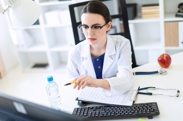 Piękna młoda dziewczyna w białej szacie siedzi przy biurku komputerowym z dokumentami i długopisem w dłoniach.