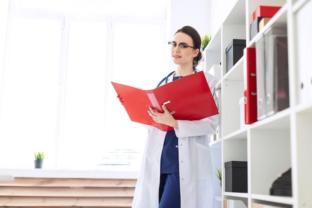 Piękna młoda dziewczyna w białej szacie stoi w pobliżu schronu i przewraca czerwony folder z dokumentami.