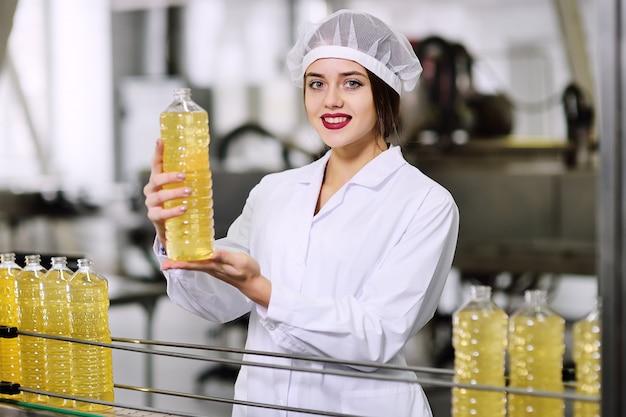 Piękna młoda dziewczyna w białym mundurze lub pracujący szlafrok z butelką oleju słonecznikowego w dłoniach na powierzchni linii do produkcji żywności rafinowanego oleju.