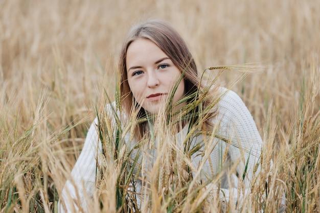 Piękna młoda dziewczyna w białym swetrze siedzi w polu pszenicy.