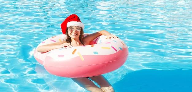 Piękna młoda dziewczyna w bikini i czapkę mikołaja z nadmuchiwanym różowym kółkiem pączka w niebieskim basenie