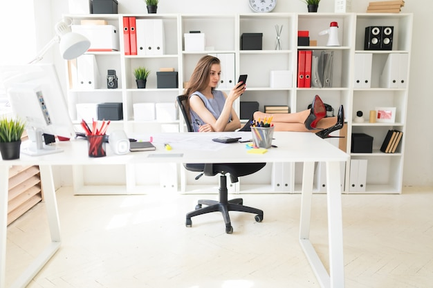 Piękna młoda dziewczyna w biurze postawiła stopy na stole i trzyma okulary i telefon.