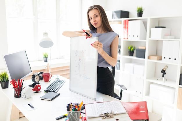 Piękna młoda dziewczyna w biurze stoi przy stole i położyła ręce na tablicy magnetycznej.