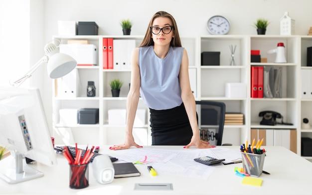 Piękna młoda dziewczyna w biurze stoi przy stole i wkłada ręce.