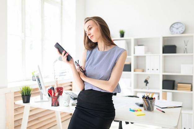 Piękna młoda dziewczyna w biurze stoi przy stole, trzyma w dłoni okulary i patrzy na ekran telefonu.