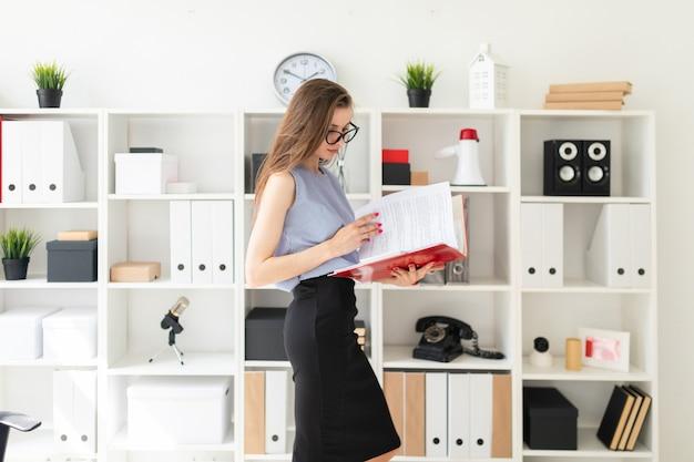 Piękna młoda dziewczyna w biurze stoi w pobliżu stojaka i przewija folder z dokumentami.