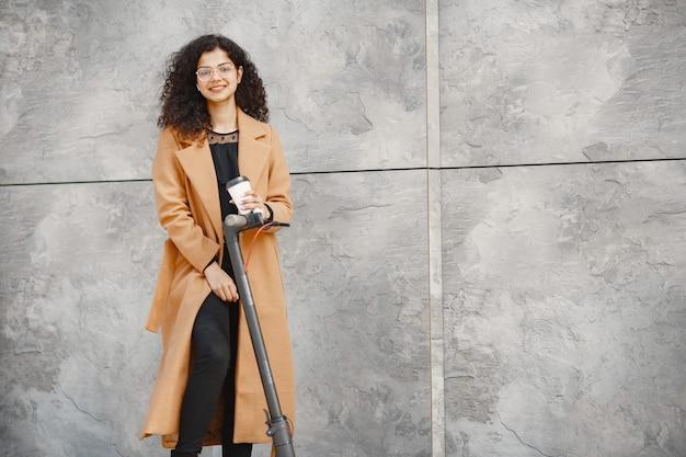 Piękna młoda dziewczyna w brązowym płaszczu. kobieta jedzie na skuterze elektrycznym.