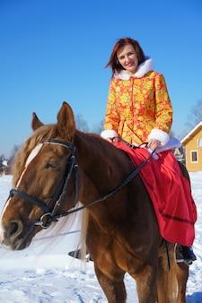 Piękna młoda dziewczyna w ciepłej żółto-czerwonej kurtce jeździ na koniu w zimowy słoneczny mroźny dzień. w sezonie zimowym uprawia sporty jeździeckie