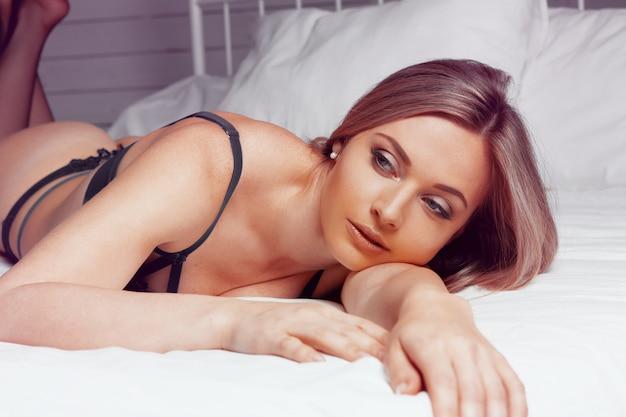 Piękna młoda dziewczyna w czarnej bieliźnie pozuje na łóżkowym zakończeniu up