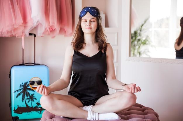 Piękna młoda dziewczyna w czarnej piżamie wczesnym rankiem ćwiczy jogę w swojej sypialni.