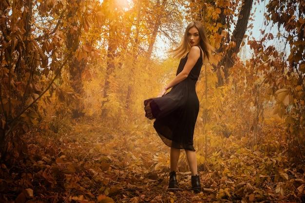 Piękna, młoda dziewczyna w czarnej sukni, pozowanie na kamery w złotej jesieni drewna na zewnątrz