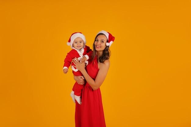 Piękna młoda dziewczyna w czerwonej sukience trzyma syna w stroju świętego mikołaja i czapce świętego mikołaja